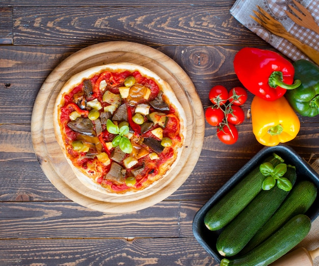 Fresh homemade pizza with different vegetables on wood