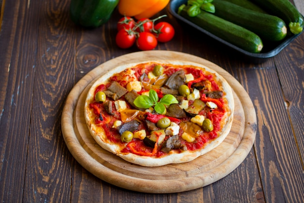 Fresh homemade pizza with different vegetables on wooden table