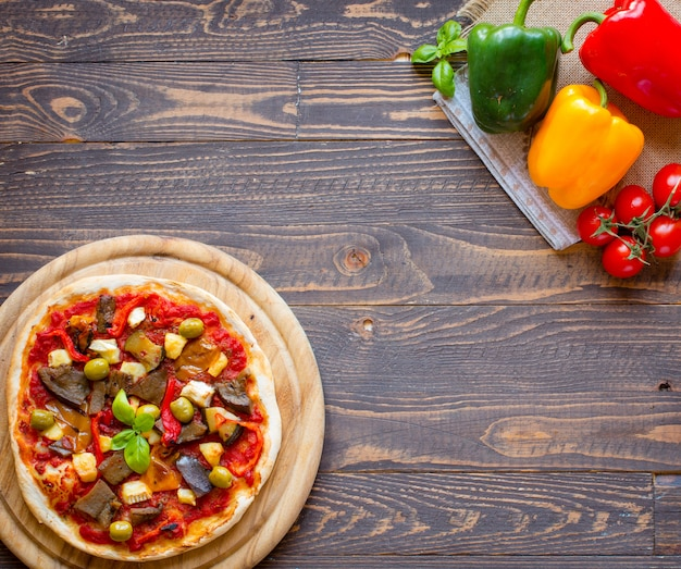 Fresh homemade pizza with different vegetables on a wooden table