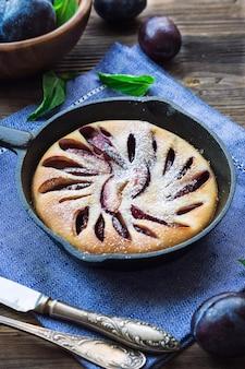 Свежий домашний сливовый пирог в сковороде железа на деревенском деревянном столе.