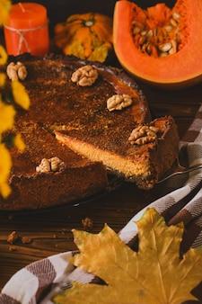 木製のテーブルに材料と秋の花を添えた、ホイップクリームとクルミの新鮮な自家製カボチャチーズケーキ