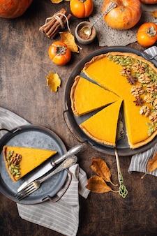 Свежий домашний тыквенный пирог на день благодарения, украшенный грецкими орехами и семенами. нарезанный на куски на винтажном подносе на деревенской фанерной поверхности. вид сверху.
