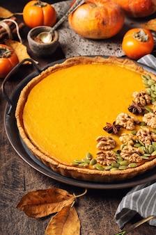 Свежий домашний тыквенный пирог на день благодарения, украшенный грецкими орехами и семенами