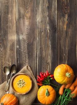 木製の素朴な背景に食材を使った新鮮な自家製カボチャスープ。上面図。スペース領域をコピーします。