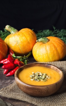 Fresh homemade pumpkin soup with ingredients on wooden rustic.
