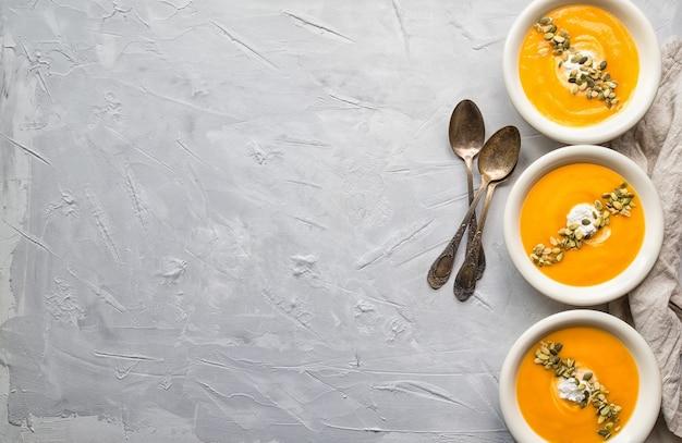 Свежий домашний суп из тыквы с сыром рикотта и семенами на сером бетоне. вид сверху.