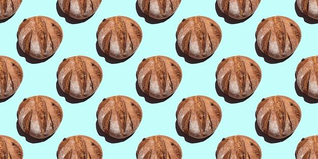 Свежий домашний деревенский ржаной круглый хлеб бесшовные модели, изолированные на синем фоне, вид сверху. может использоваться в качестве пищевого фона, основы для текстиля, упаковки
