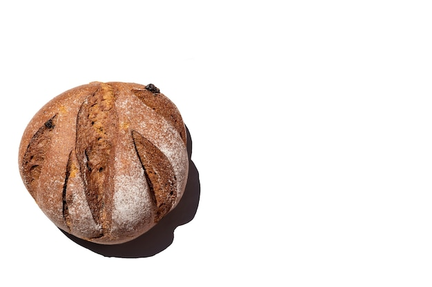 Fresh homemade rustic rye round with raisins bread isolated on white surface, top view, copy space.