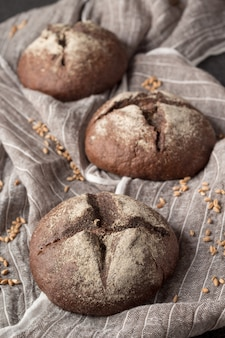 Fresh homemade rye buns on grey cloth