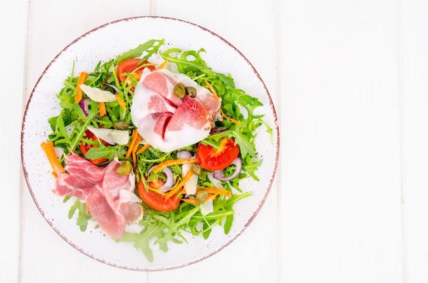 Fresh homemade salad with arugula, jamon, rucola, tomatoes, parmesan.