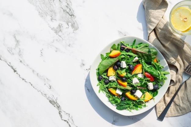 Свежий домашний салат с нектаринами черники, рукколой, шпинатом и сыром фета