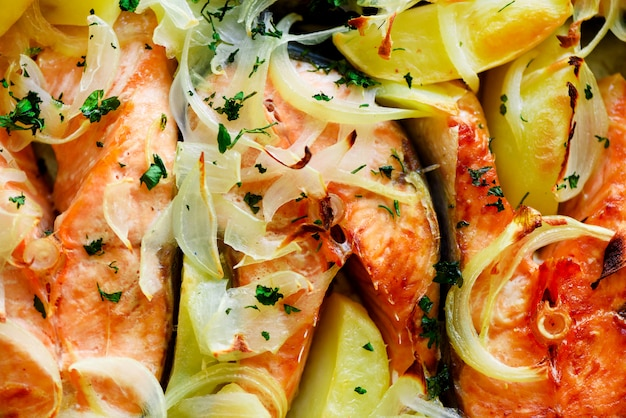 Fresh homemade salmon steaks with fried potatoes, onions and spices. food background