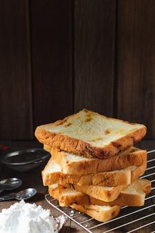 Свежий домашний нарезанный хлеб уложен на деревянный стол темный фон текстуры