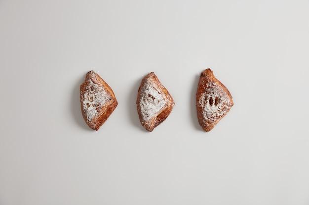 Freschi piccoli panini sfoglia fatti in casa riempiti con qualcosa di gustoso, in polvere con zucchero, isolato su sfondo bianco. deliziosi pasticcini dolci. cottura appetitosa fresca. cibo spazzatura e concetto di nutrizione