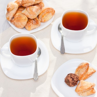 Свежее домашнее сахарное печенье с чаем на белом столе с солнечными огнями. доброе утро или дневная концепция.