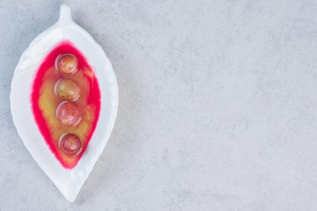 Свежий домашний сладкий десерт, белая тарелка на сером фоне.