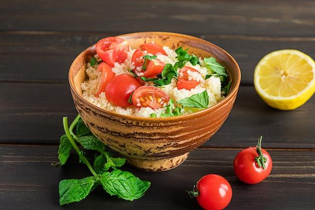 新鮮な自家製タブーリまたはタブーリサラダ、ダークウッドの表面に食材の側面図