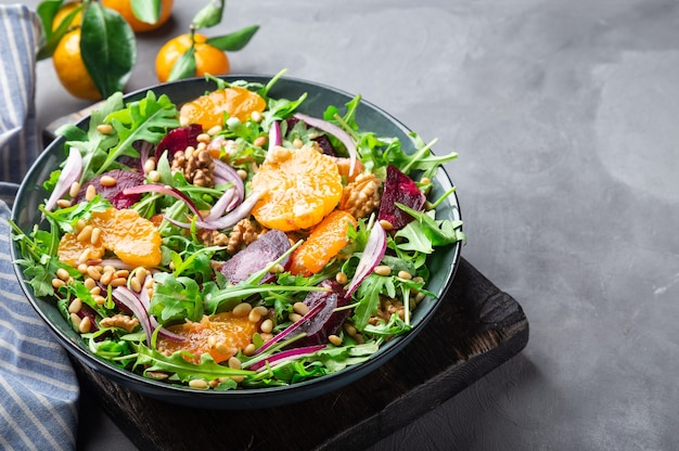 Свежий домашний салат из мандарина и свеклы с грецкими орехами рукколой и кедровыми орешками на бетонном фоне