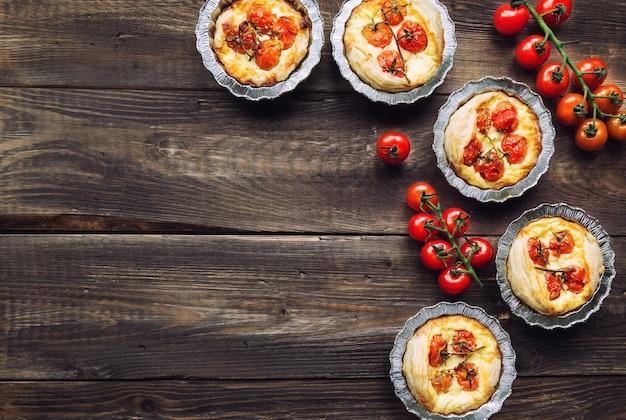 Свежие домашние пироги с помидорами черри и козьим сыром на деревенском деревянном.