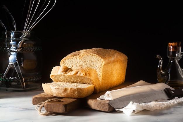 Fresh homemade toast bread on the kitchen table, dark background.