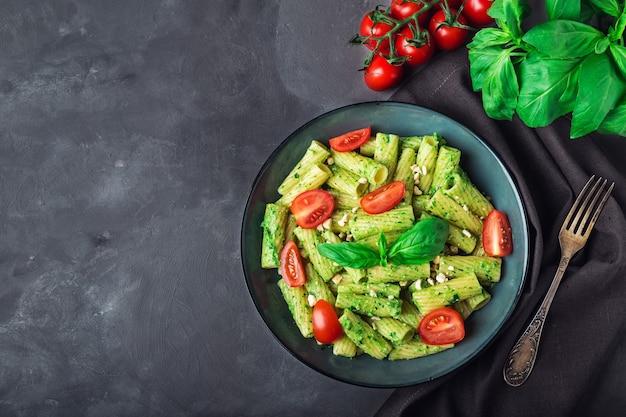채식주의 페스토 소스, 캐슈 너트, 체리 토마토와 회색 콘크리트 배경에 신선한 홈 메이드 tortiglioni 파스타. 평면도. 텍스트를위한 공간.