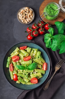 채식주의 페스토 소스, 캐슈 너트, 체리 토마토와 회색 콘크리트 배경에 신선한 홈 메이드 tortiglioni 파스타. 평면도.