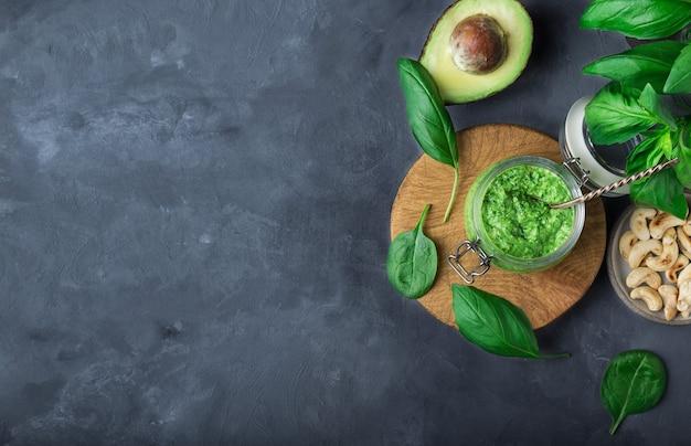 Свежий домашний веганский соус песто с базиликом, шпинатом, орехами кешью и авокадо в банке на сером бетонном фоне с ингредиентами. вид сверху. место для текста.