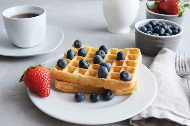 Fresh homemade viennese or belgian waffles with blueberries and strawberries on a white plate