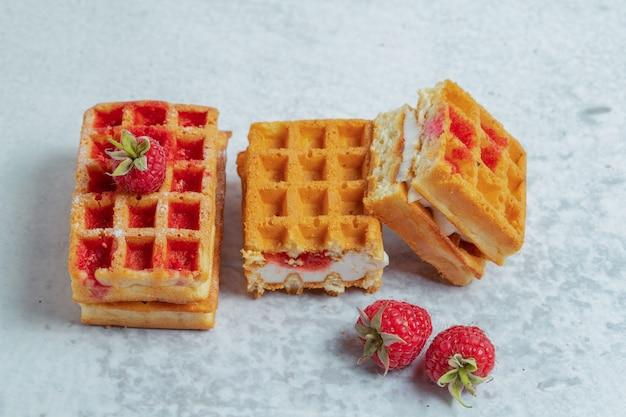 Кусочки свежих домашних вафель с малиной на серой поверхности.