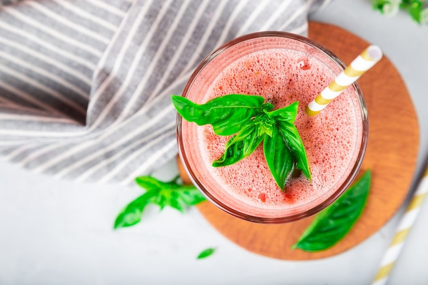 Fresh homemade watermelon and basil smoothie in glass on white concrete background