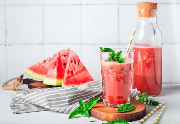 Fresh homemade watermelon and basil smoothie in glass on white tile background