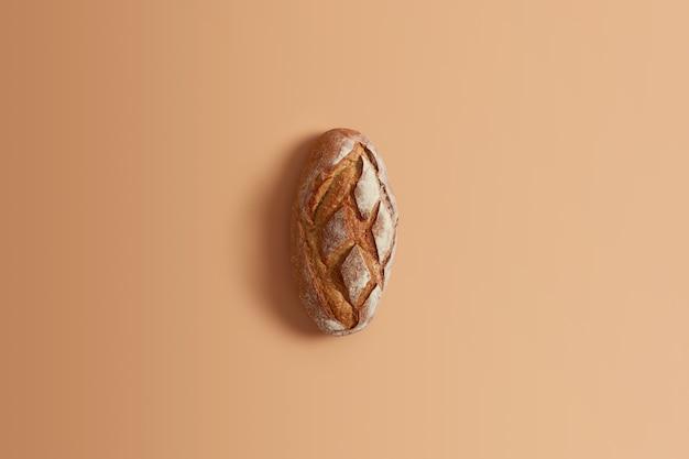 베이지 색 배경에 고립 된 전체 호밀로 만든 신선한 수 제 밀 빵. 당신의 소비를위한 전체 덩어리. 구운 제품. 누룩이나 사워 도우로만 효모없이 준비된 글루텐 프리 유기농 제품