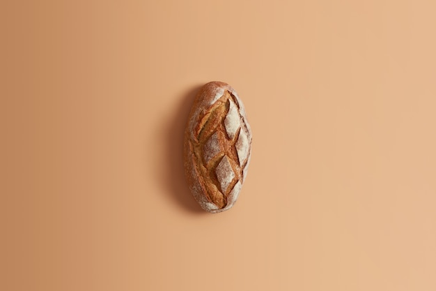 Fresh homemade wheat bread made of whole rye isolated on beige background. whole loaf for your consumption. baked goods. gluten free organic product prepared without yeast, only on leaven or sourdough
