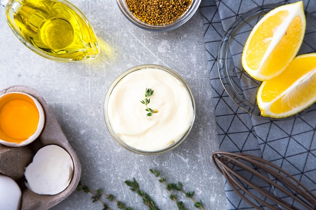 Fresh homemade white sauce mayonnaise and ingredients eggs, lemon olive oil on stone background. top view