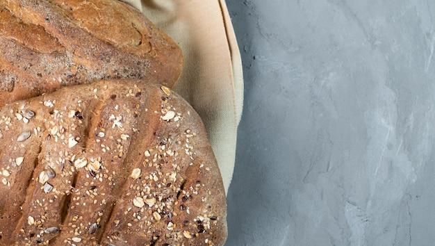 灰色の背景に新鮮な自家製の健康的なパン、クローズアップ、灰色の背景に上面図。左側にパン、右側にテキスト用の空きスペース。