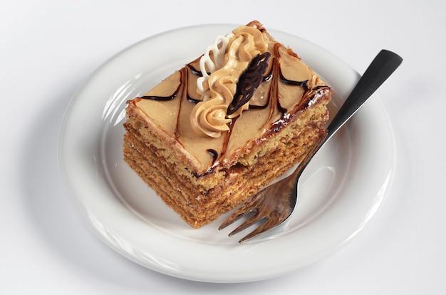 흰색 바탕에 접시에 크림과 함께 신선한 꿀 케이크