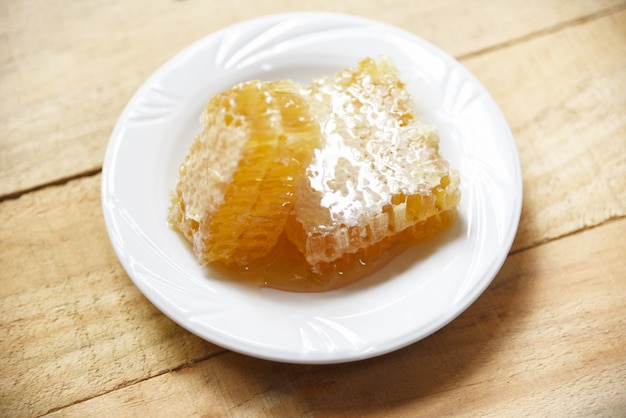 Fresh honey - close up of yellow sweet honeycomb slice on white plate natural healthy food