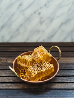 Fresh honey comb pieces in copper utensil on wooden table