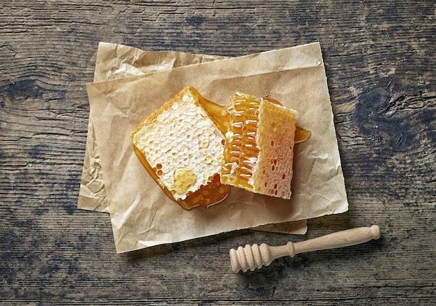 소박한 나무 식탁에 있는 신선한 꿀 빗 조각, 위쪽 전망