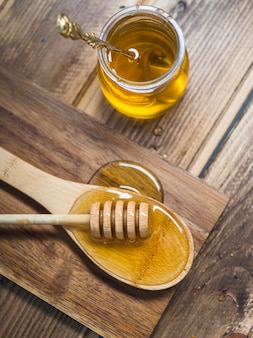 Fresh honey dipper on wooden spoon and pot with spoon