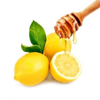 Свежий мед капает с ложки на лимон. на белом.