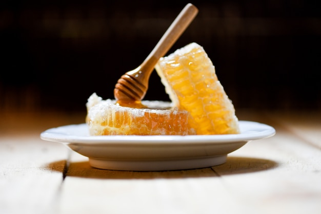 Fresh honey healthy food yellow sweet honeycomb slice with wooden dipper on plate and dark