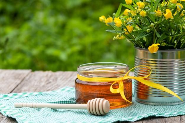 Свежий мед в стеклянной банке на природе.