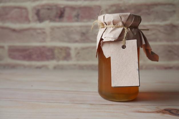Свежий мед в стеклянной банке с бумажной пустой этикеткой