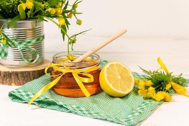 Свежий мед в стеклянной банке с лимоном.