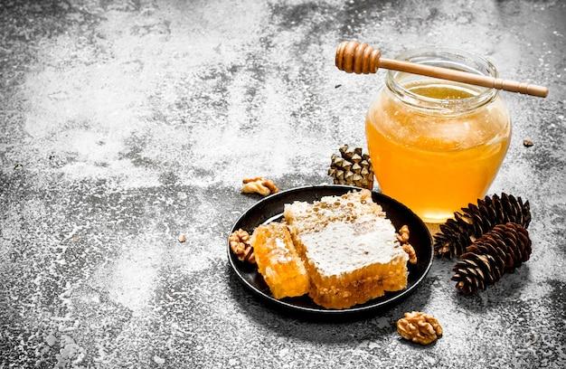 瓶に入った新鮮な蜂蜜とナッツ入りのハニカム。素朴な背景に。