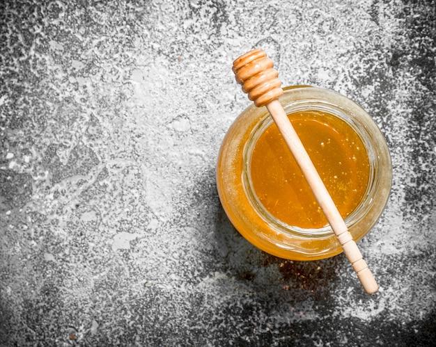 Свежий мед в банке с деревянной ложкой. на деревенском фоне.