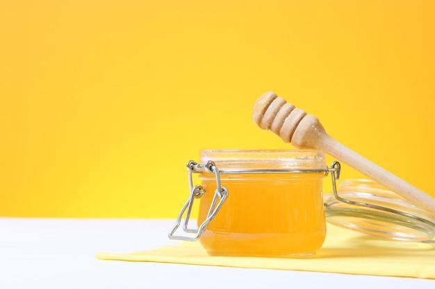 Свежий мед на столе крупным планом на цветном фоне