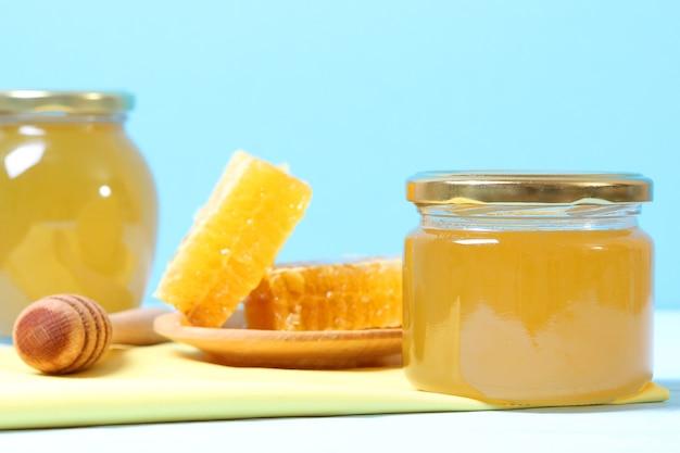 色付きの背景のテーブルのクローズアップに新鮮な蜂蜜