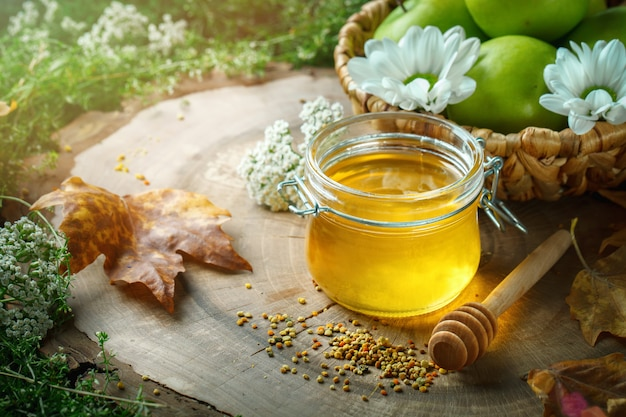 Fresh honey, pollen and ripe apples on a wooden table